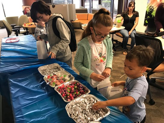 As part of Take Your Child to Work Day, children of employees at AT&T's Global Legal Demand Center in North Palm Beach put together 50 goody bags for officers with the Jupiter Police Department as a thank you for their service. Putting candy in the goody bands are, from left, Logan Sukanec, Ava Rick and AJ Signore.