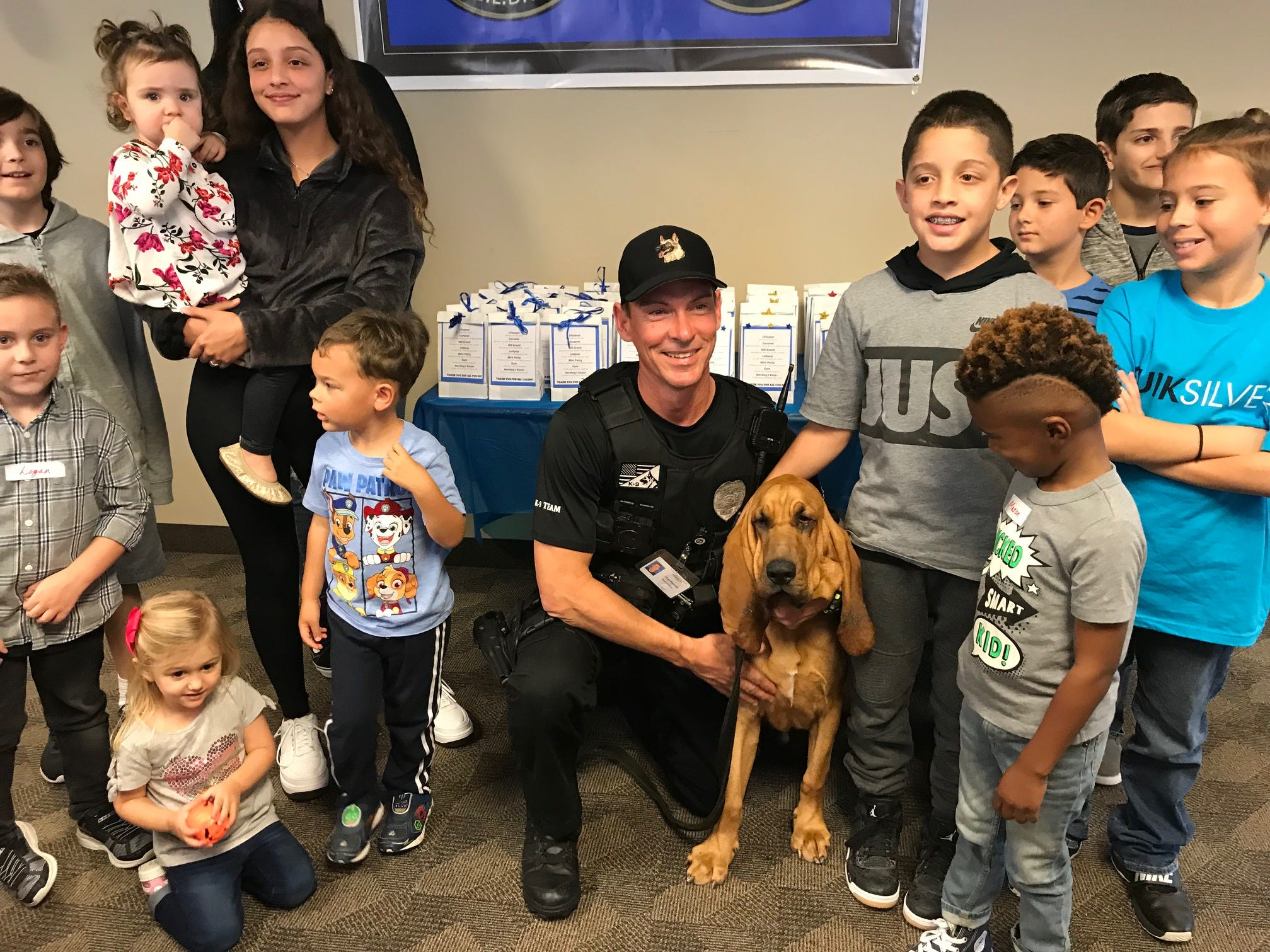 Employees and children at AT&T's Global Legal Demand Center in North Palm Beach with Jupiter Police K9 Officer Chad Norman and K9 Bandit, a blood hound.