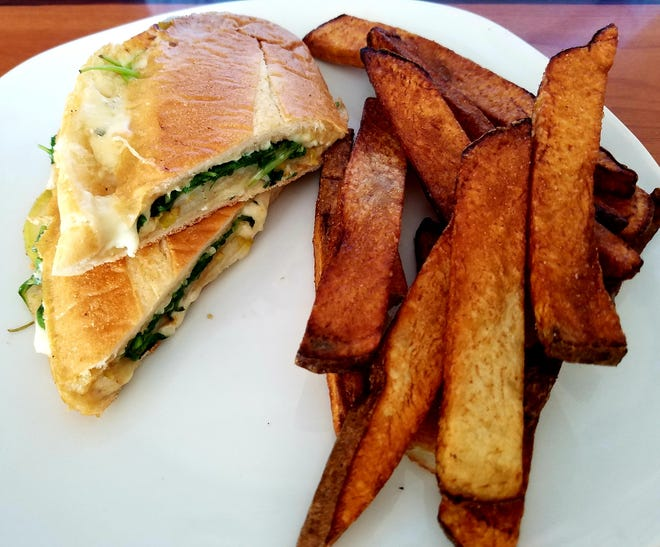 The apple bacon pear sandwich was served with bacon, blue cheese, sliced pear, jalapeno honey and arugula pressed on a buttered hoagie roll. Shown with hand-cut steak fries.
