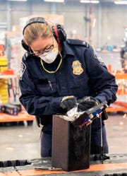 This photo provided by U.S. Customs and Border Protection shows an officer extracting methamphetamine from a loudspeaker on Jan. 11 at the Los Angeles-Long Beach seaport.  Australian police arrested six people after what authorities said Friday was the largest single seizure of methamphetamine in the United States and the biggest drug haul bound for Australia.