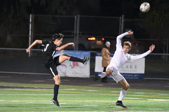 Newbury Park senior Victor Ke clears the ball under pressure from a St. Francis player on Thursday in the first round of the CIF-Southern Section boys soccer playoffs. Newbury Park won, 1-0.