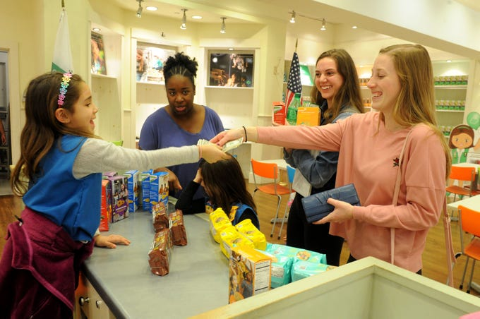 Talia Pannier, left, makes a cookie sale to Lizzi Raker and Kaylie Scofield at the Girl Scouts' storefront at The Oaks mall. Watching is Etevia Bragar. The Girl Scouts of California's Central Coast opened a storefront a few days ago at the mall in Thousand Oaks.