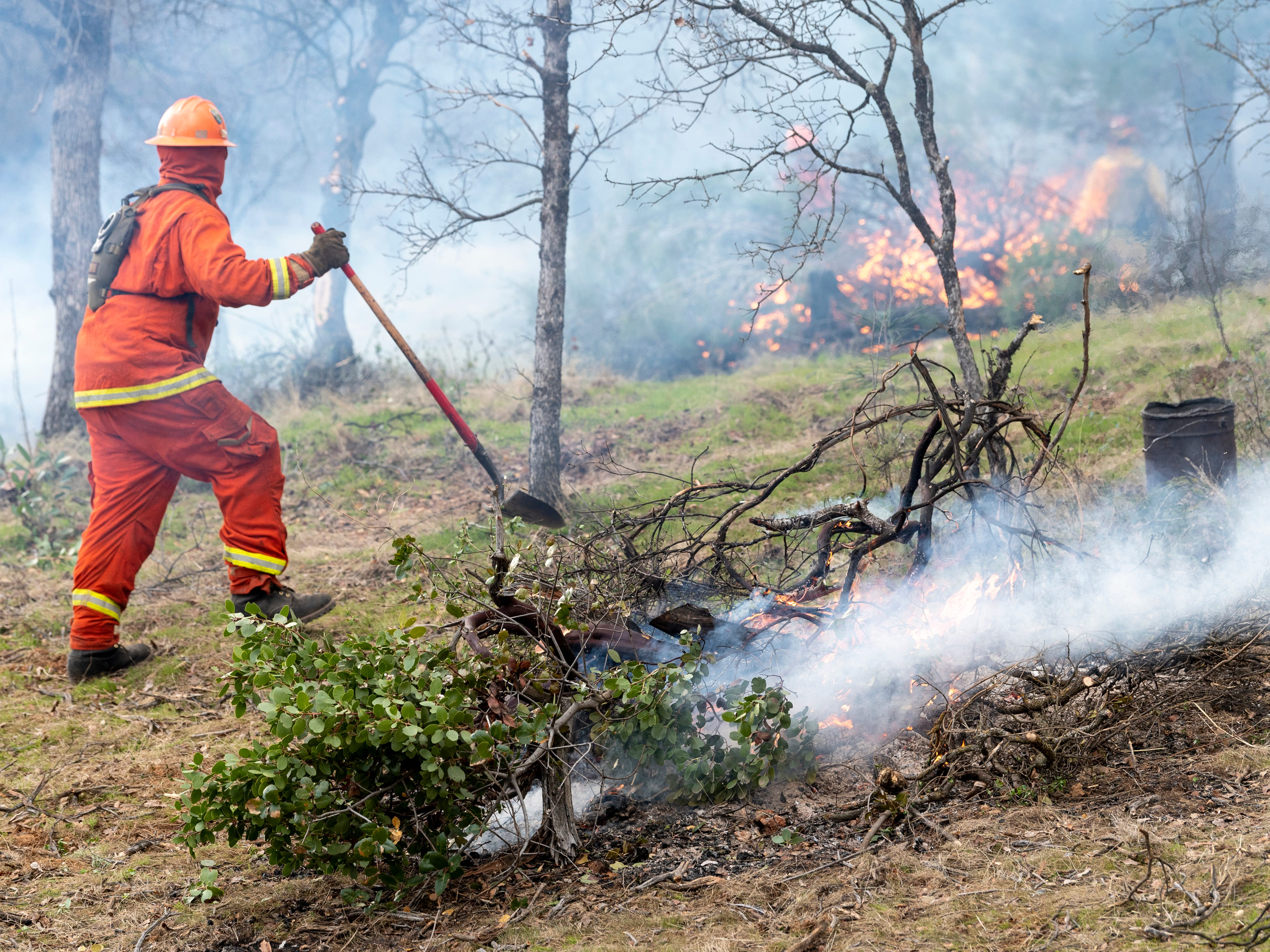 Sugar Pine Conservation Camp inmates burn brush piles to reduce the fire hazard in a greenbelt located in between residential areas in west Redding on Wednesday, Feb. 6, 2019.