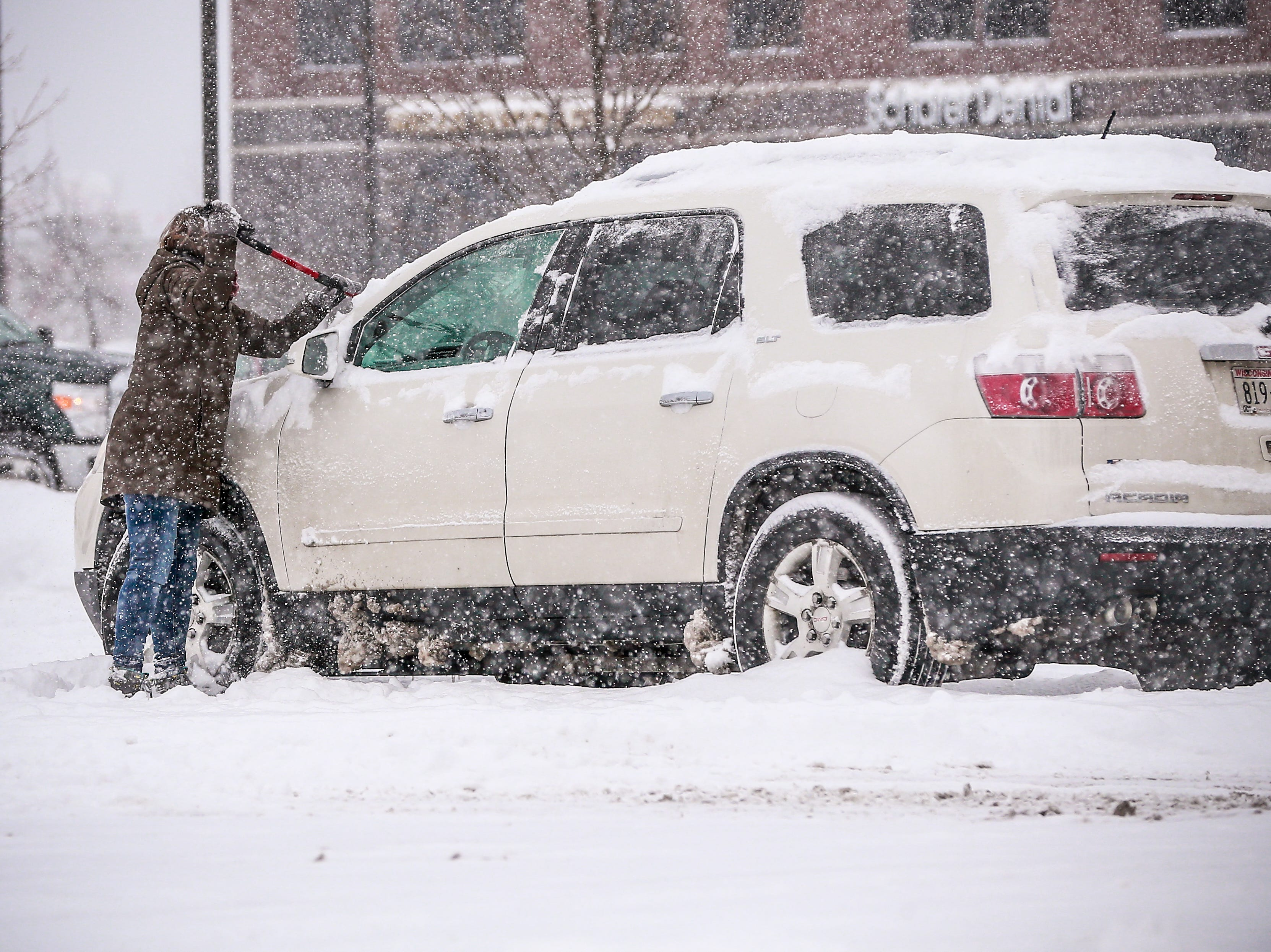 A person brushes snow off from her vehicle during the snowstorm Thursday, Feb. 07, 2019, in Wausau, Wis. T'xer Zhon Kha/USA TODAY NETWORK-Wisconsin