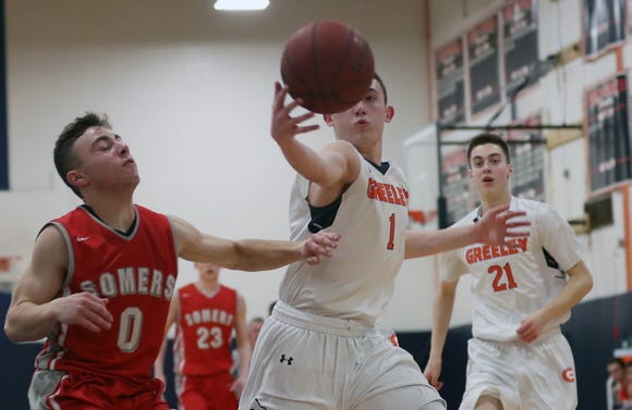 Greeley's Michale Saloie grabs a loose ball in front of Somers' Bennett Loiter (0) during boys basketball action at Horace Greeley High School Feb. 7,  2019. Greeley won the game 71-47.