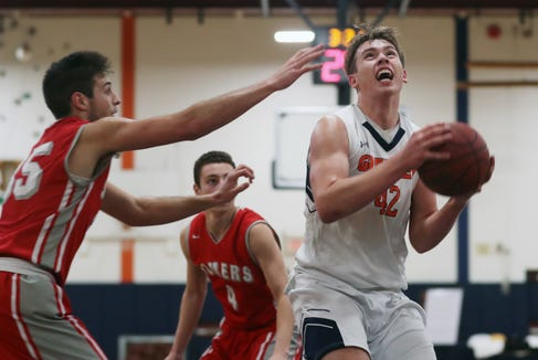Greeley's Nick Townsend (42) drives to the basket in front of Somers' Nick Maestri (35) during boys basketball action at Horace Greeley High School Feb. 7,  2019. Greeley won the game 71-47.