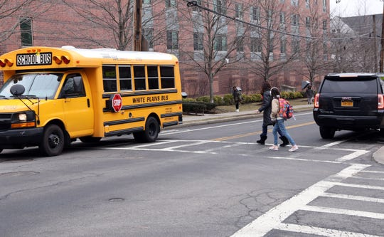 A student crosses Main Street with an adult after school at Eastview Middle School Feb. 7, 2019 in White Plains.