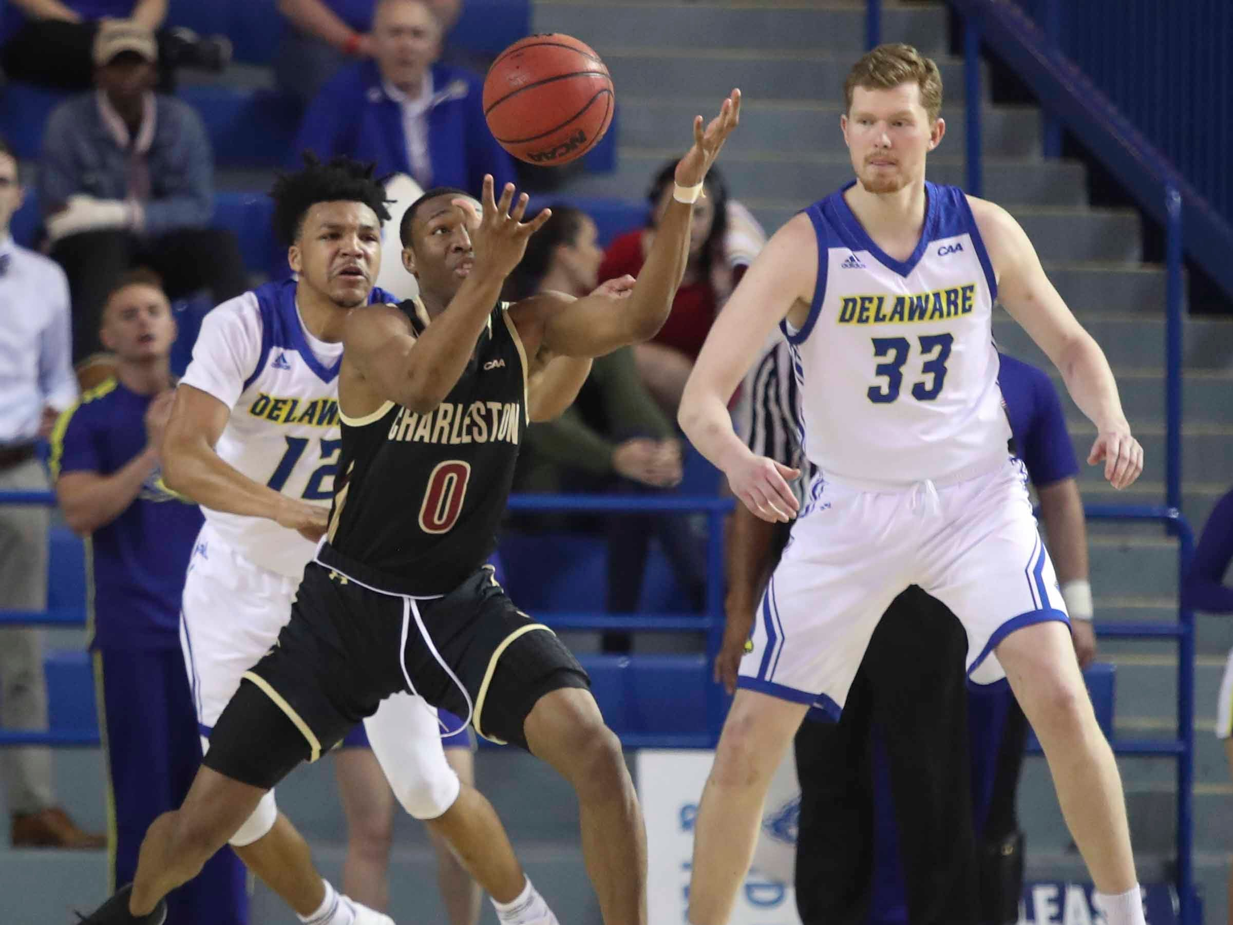 Charleston's Jaylen Richard (0) temporarily loses the ball in front of Delaware's Ithiel Horton (left) and Collin Goss in the first half at the Bob Carpenter Center Thursday.
