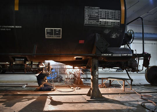 An Eagle Railcar Services welder makes repairs to a large railroad tank car as it sits on jack stands. The company recently installed two 20-ton cranes that can lift a train car for repairs.