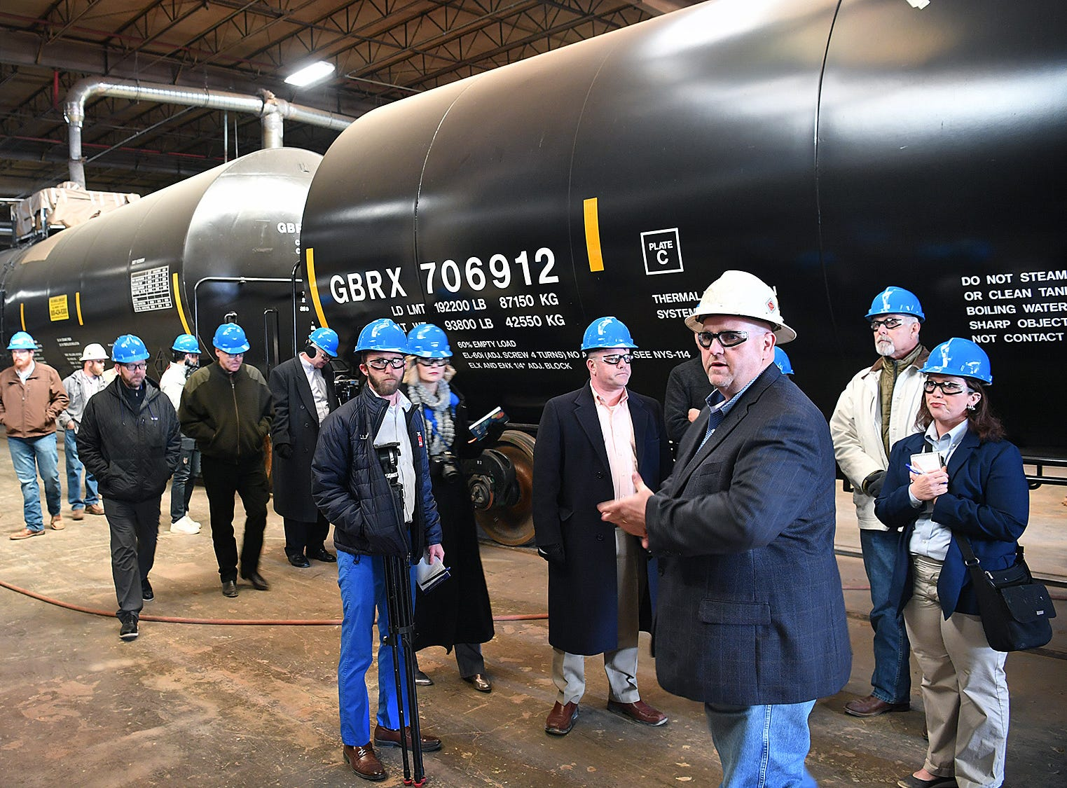 Plant Manager James Bullard, white hardhat, conducts a tour of Eagle Railcar Services for community leaders and the media Friday morning.