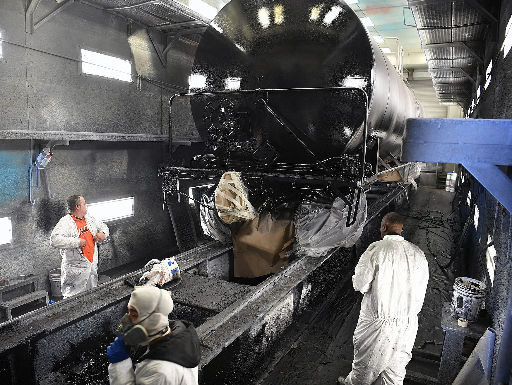 Paint booth workers prepare to finish a paint job on a large tankcar at Eagle Railcar Services Friday.