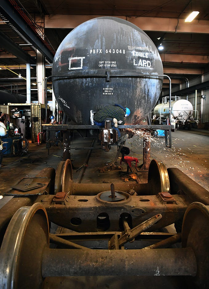 An employee of Eagle Railcar Services uses a metal grinder during a tank car repair Friday. The company opened in 2015, currently employ 150 people with plans to expand later this year.