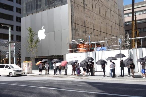 Customers in Tokyo wait their turn to enter an Apple Store