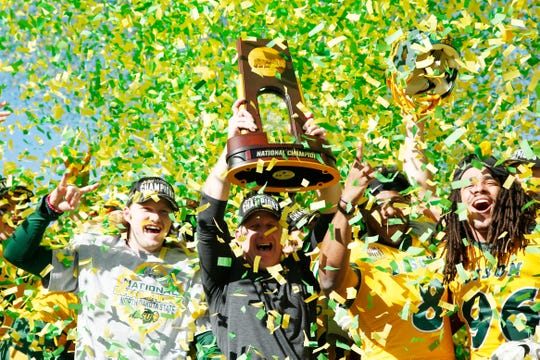 North Dakota State head coach Chris Klieman holds up the FCS Championship trophy after a win against Eastern Washington.