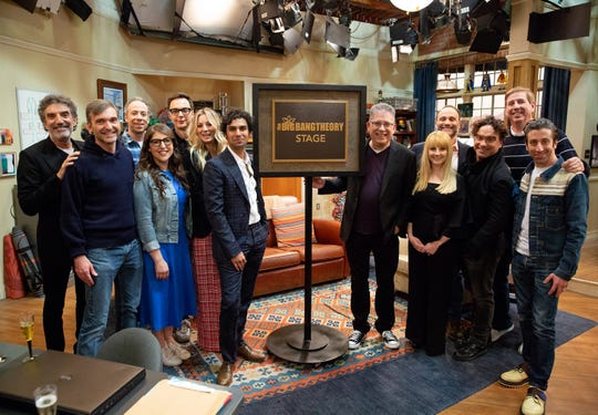 Executive producers Chuck Lorre, left, and Steve Hollland and stars Kevin Sussman, Mayim Bialik, Jim Parsons, Kaley Cuoco and Kunal Nayyar stand to the left of 'The Big Bang Theory' stage plaque, with executive producer Bill Prady, star Melissa Rauch, executive producer Steven Molaro, star Johnny Galecki, director Mark Cendrowski and star Simon Helberg to the right. (Photo: Warner Bros.)