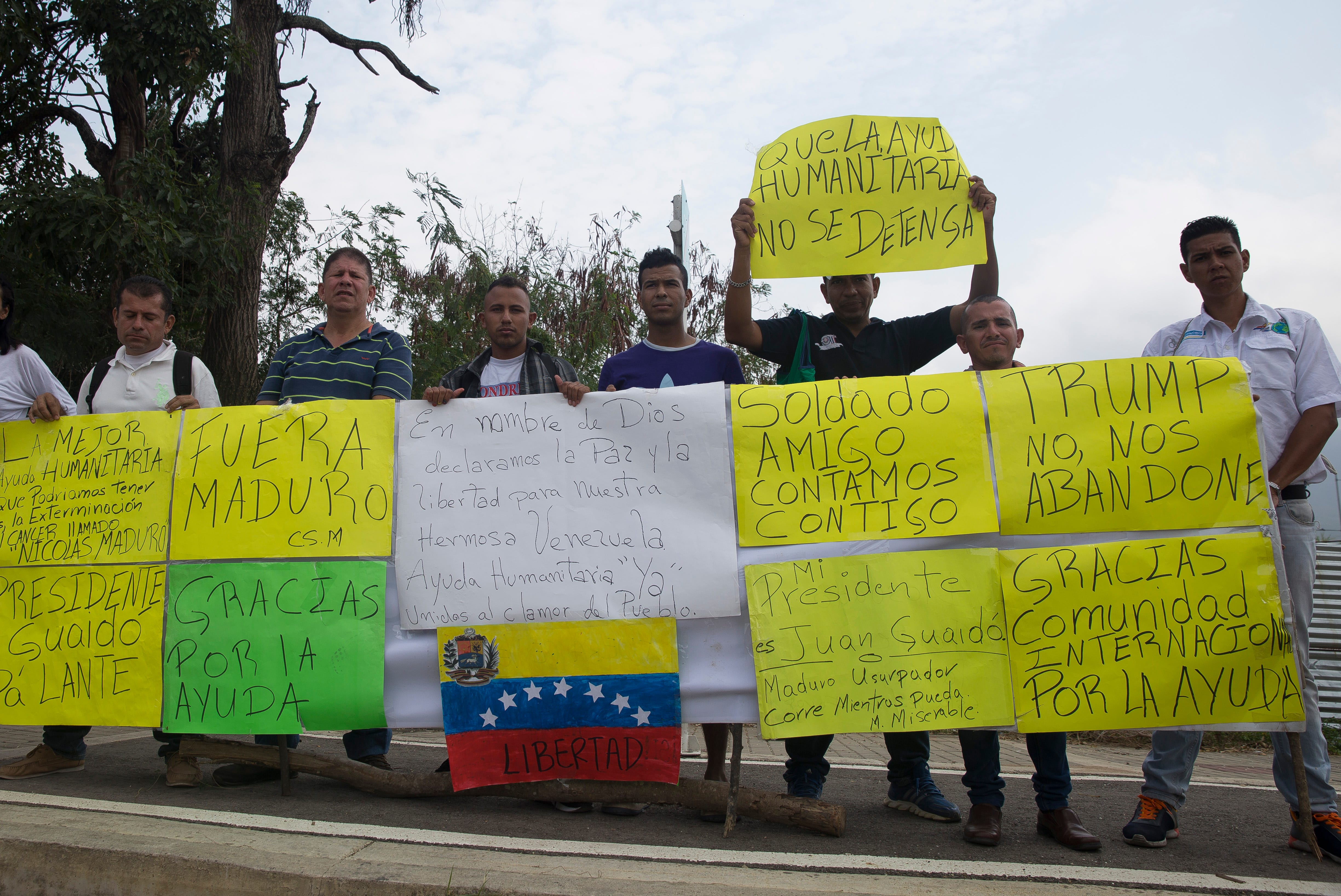 "Protestors carrying signs reading ""Trump don't abandon us"" stand outside of the entrance to the facility housing the first of the United States humanitarian aid in Cœcuta, Colombia on Feb. 8, 2019. The food and medicine is being blocked from crossing into Venezuela by the Maduro-controlled Venezuelan military."