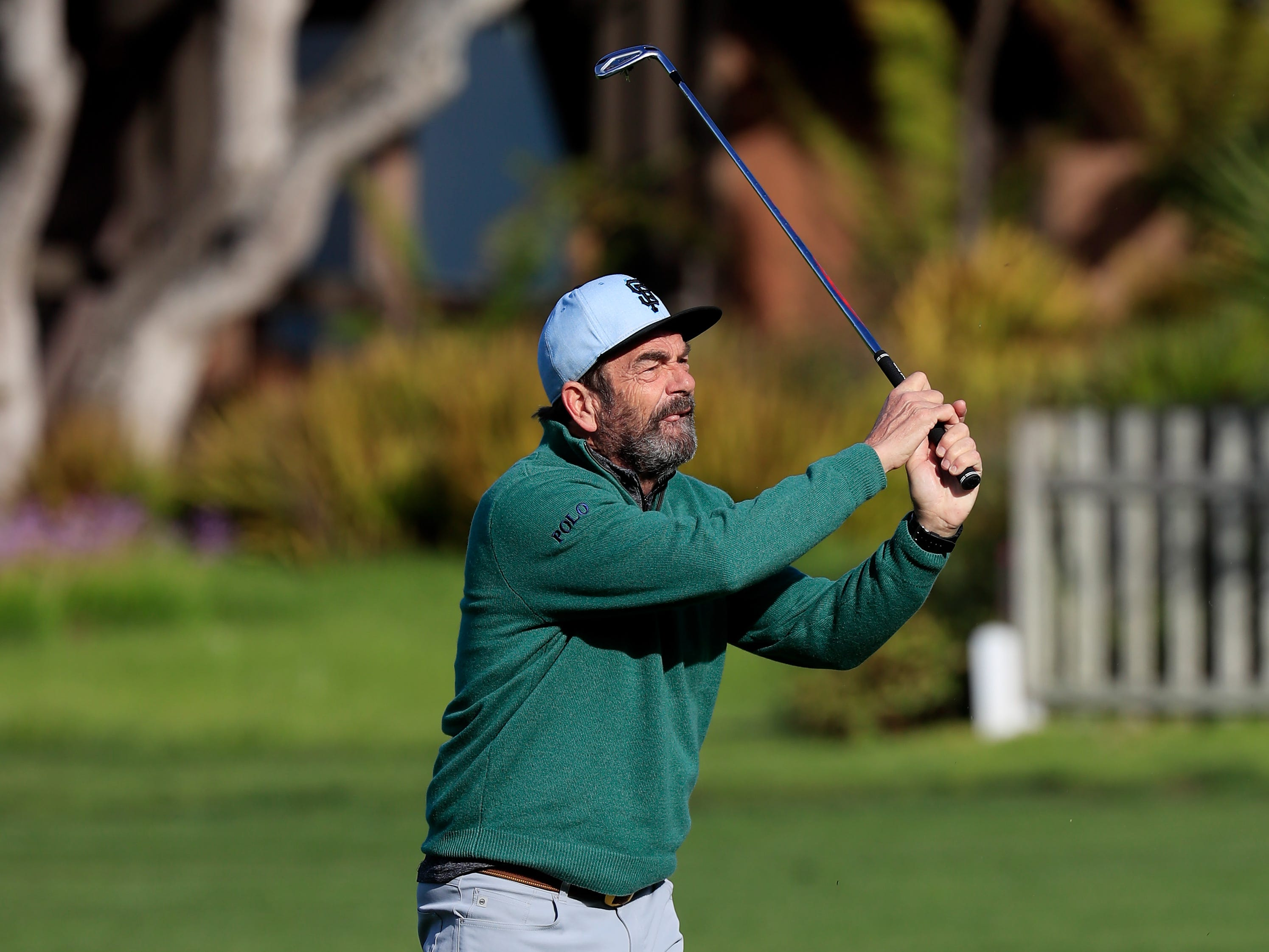 Singer Huey Lewis plays a shot during the first round of the AT&T Pebble Beach Pro-Am.