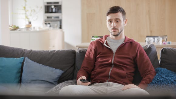 Young man sitting on sofa and watching TV in living room.