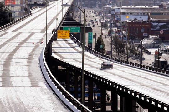A car belonging to a state agency drives over a light coating of snow on the otherwise closed Alaskan Way viaduct in near-freezing weather on Feb. 5, 2019 in Seattle.
