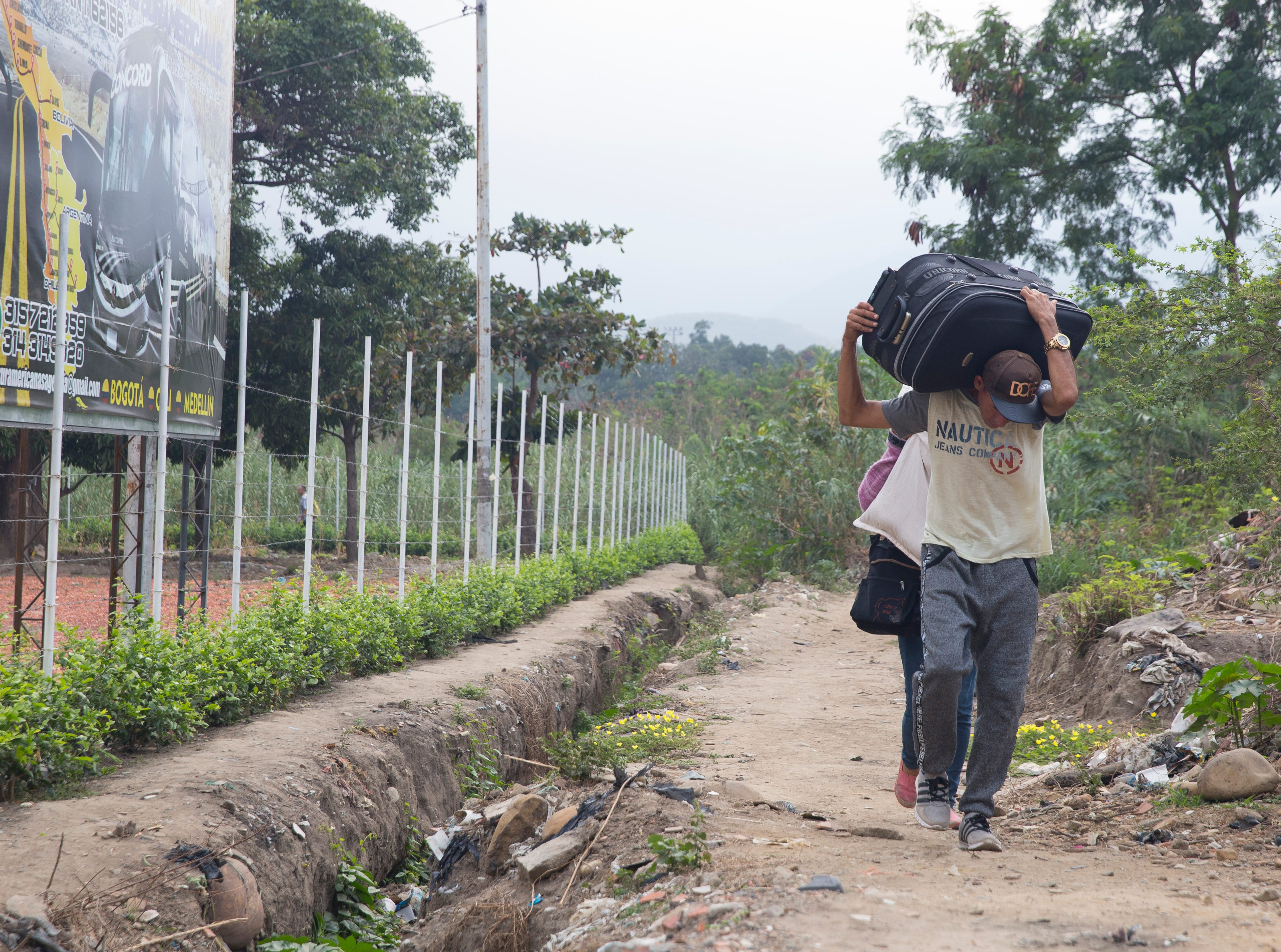Migrants along the Colombia-Venezuela border sprint with their luggage hoisted over their heads after crossing illegally by boat 50 meters from the legal border checkpoint on Feb 6, 2019. Many migrants are forced to cross illegally because it's become nearly impossible in Venezuela to obtain documents like passports and IDs.