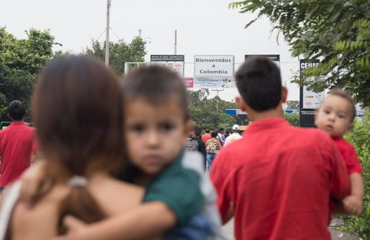Families of Venezuelans flee their country, crossing the Colombia-Venezuela border on Feb. 6, 2019.