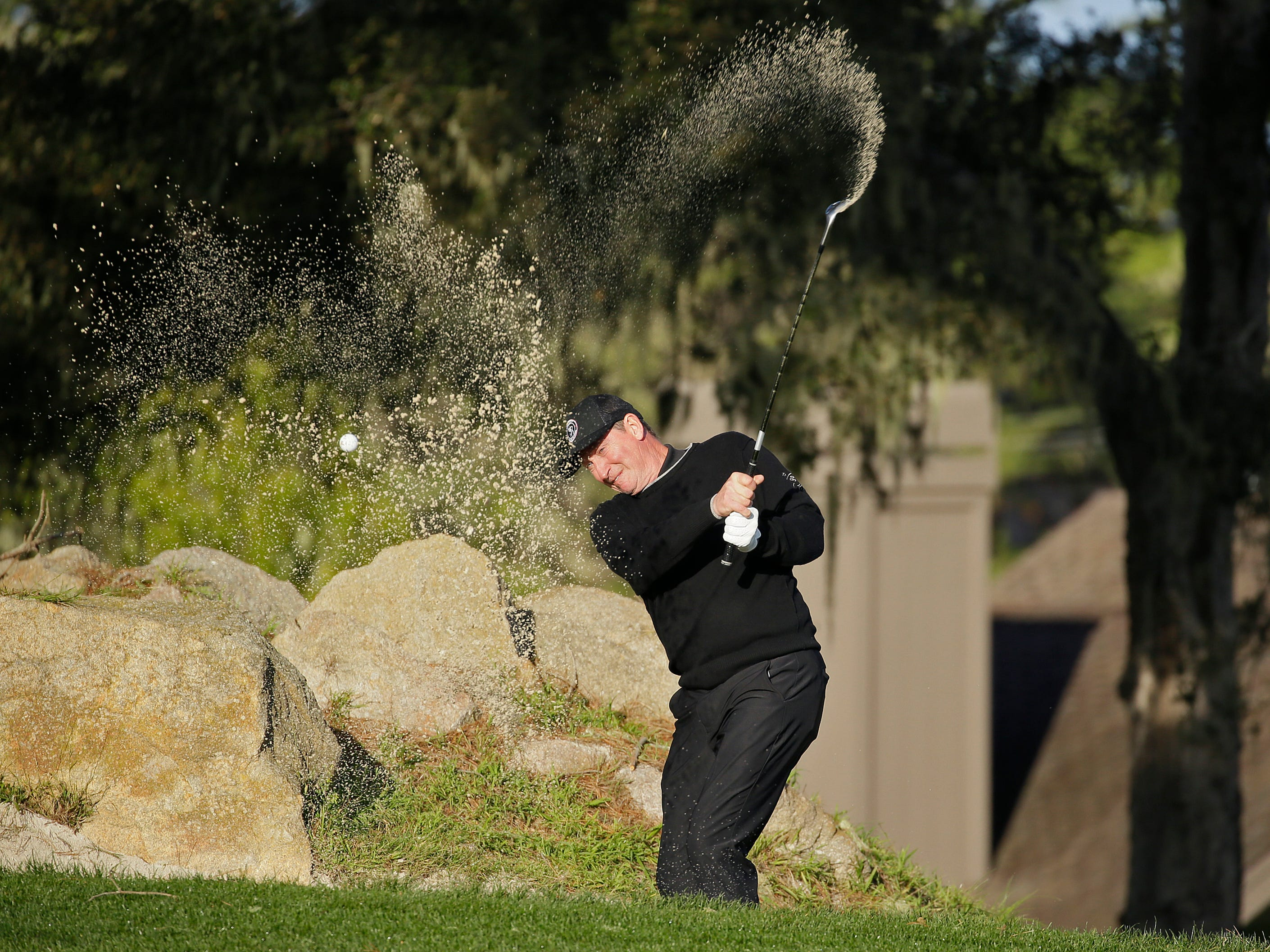 Hockey legend Wayne Gretzky hits out of a bunker onto the second green of the Monterey Peninsula Country Club Shore Course during the first round of the AT&T Pebble Beach National Pro-Am.