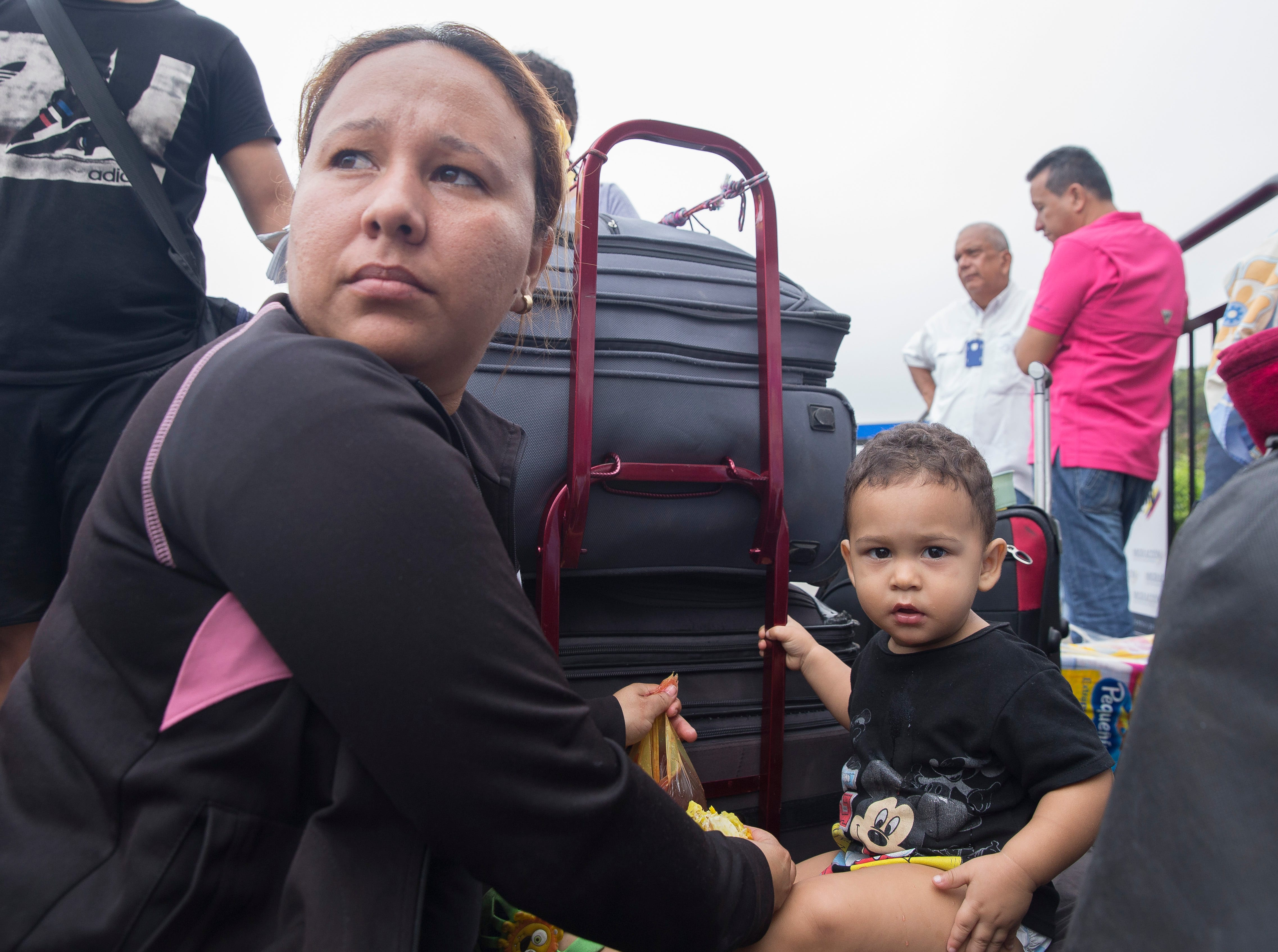 Isa Gallego sits with her baby and peers toward the Colombia-Venezuela border bridge on Feb. 6, 2019. Gallego's family sits among luggage, preparing to return to Venezuela with a new hope.