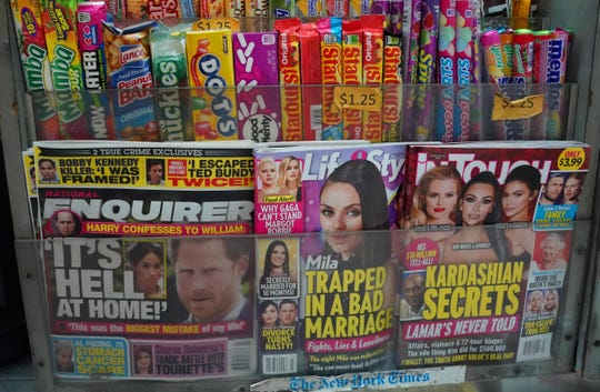 A copy of the National Enquirer is seen at a newspaper vendor's shop on Third Avenue in midtown New York City Friday alongside other titles by AMI, the tabloid publisher at the heart of growing scandals involving President Donald Trump and Amazon founder Jeff Bezos.