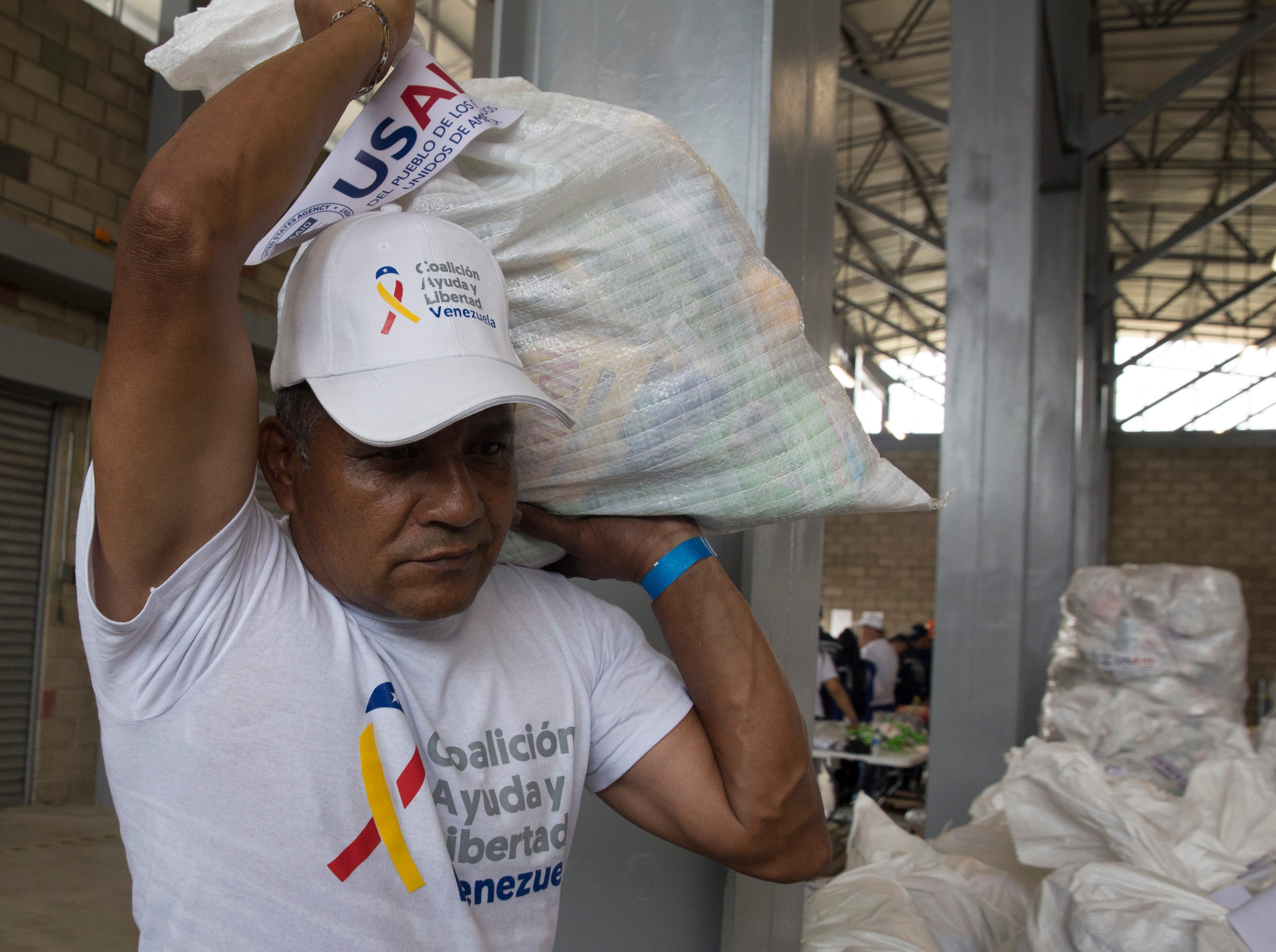 Men and women pack white sacks full of food and medicine from the United States for the Venezuelan people on Colombia-Venezuela border on Feb. 8, 2019.
