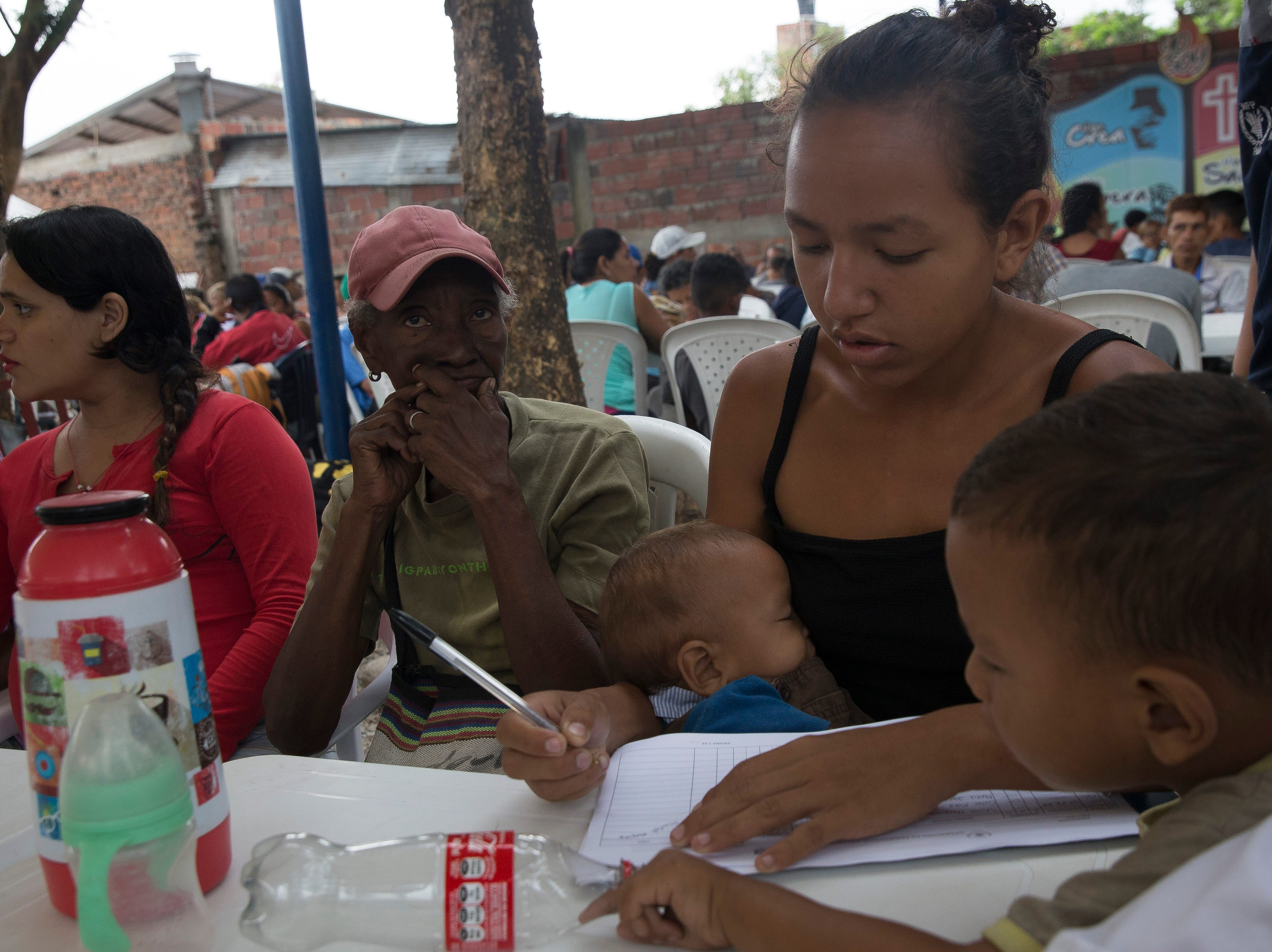 A Venezuelan family writes down their information to receive free breakfast along the Colombia-Venezuela border in Cœcuta, Colombia on Feb. 8, 2019.