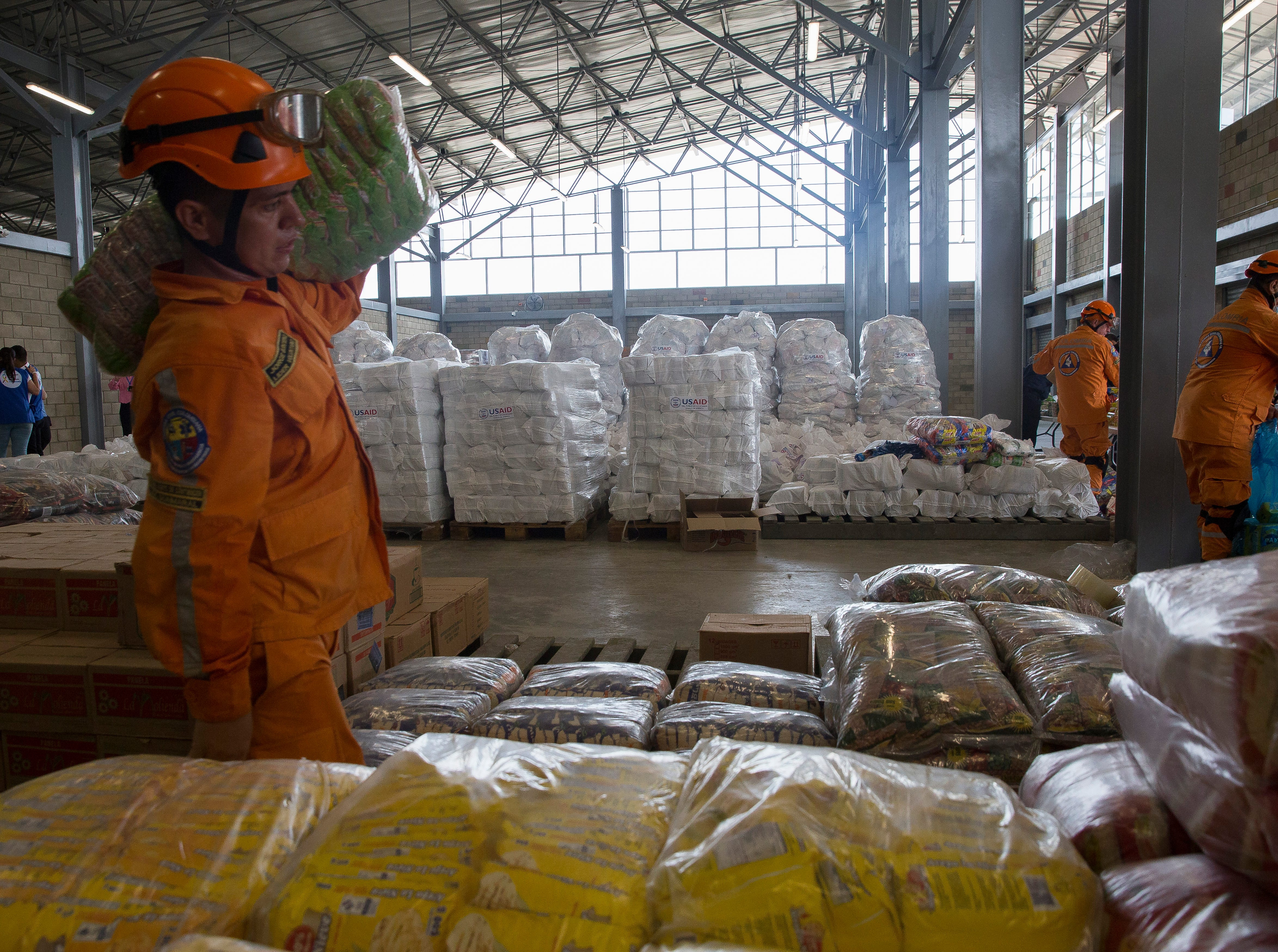 An aid worker carries a sack of lentils to be packed in white sacks of US humanitarian aid to be sent to the Venezuelan people on Colombia-Venezuela border on Feb. 8, 2019.