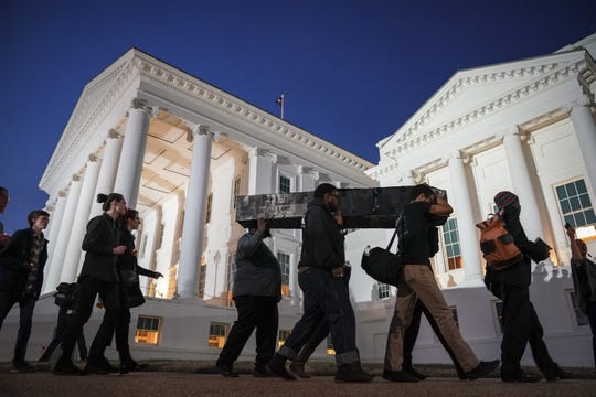 Protestors carry a fake coffin, to symbolize what they call the death of the Democratic Party, toward the Virginia State Capitol, February 7, 2019 in Richmond, Virginia. Virginia state politics are in a state of upheaval, with Governor Ralph Northam and State Attorney General Mark Herring both admitting to past uses of blackface and Lt. Governor Justin Fairfax accused of sexual misconduct.