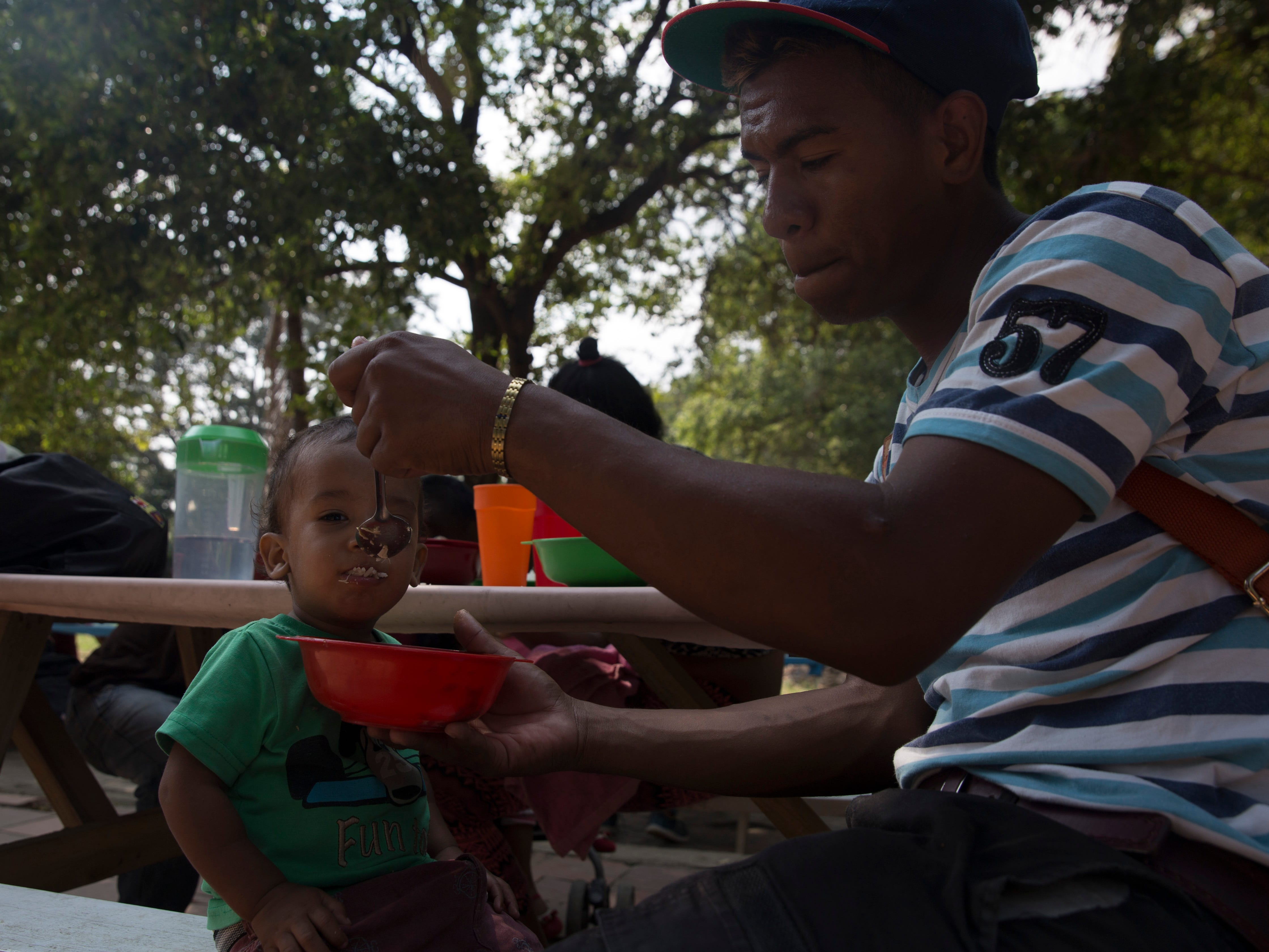 Venezuelan migrant Ricardo Toreabo feeds his two-year-old son at a soup kitchen in Cœcuta, Colombia on Feb 6, 2019. The family has been sleeping on the streets since they arrived in Colombia days before.