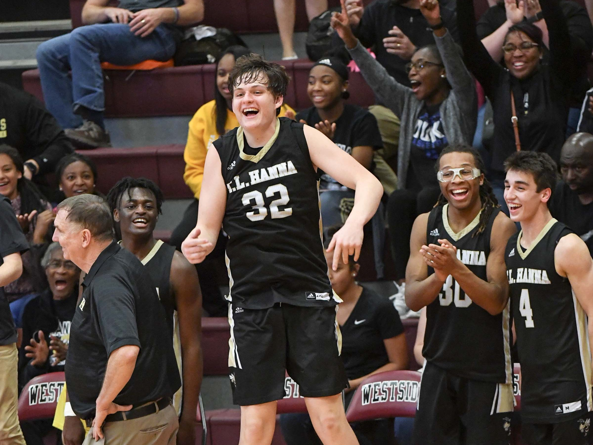 TL Hanna junior John Haddock Rogers(32) and teammates celebrate in the closing seconds of a 70-45 win at Westside High School in Anderson Friday.