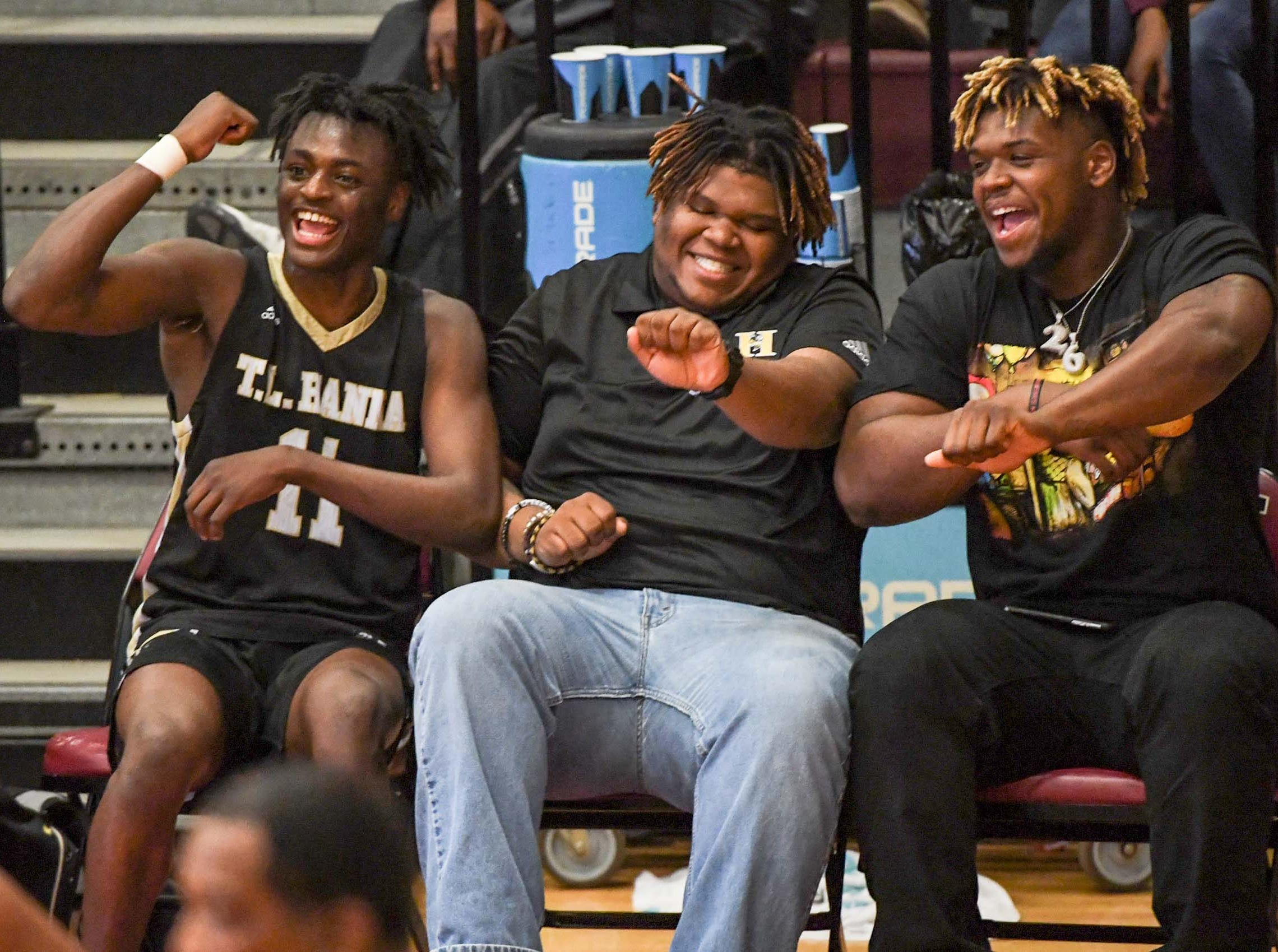 TL Hanna senior Ja'hiem Handy(11), left, watches his team close out a 70-45 win at Westside High School in Anderson Friday. Football player Zacch Pickens, right, joins in.