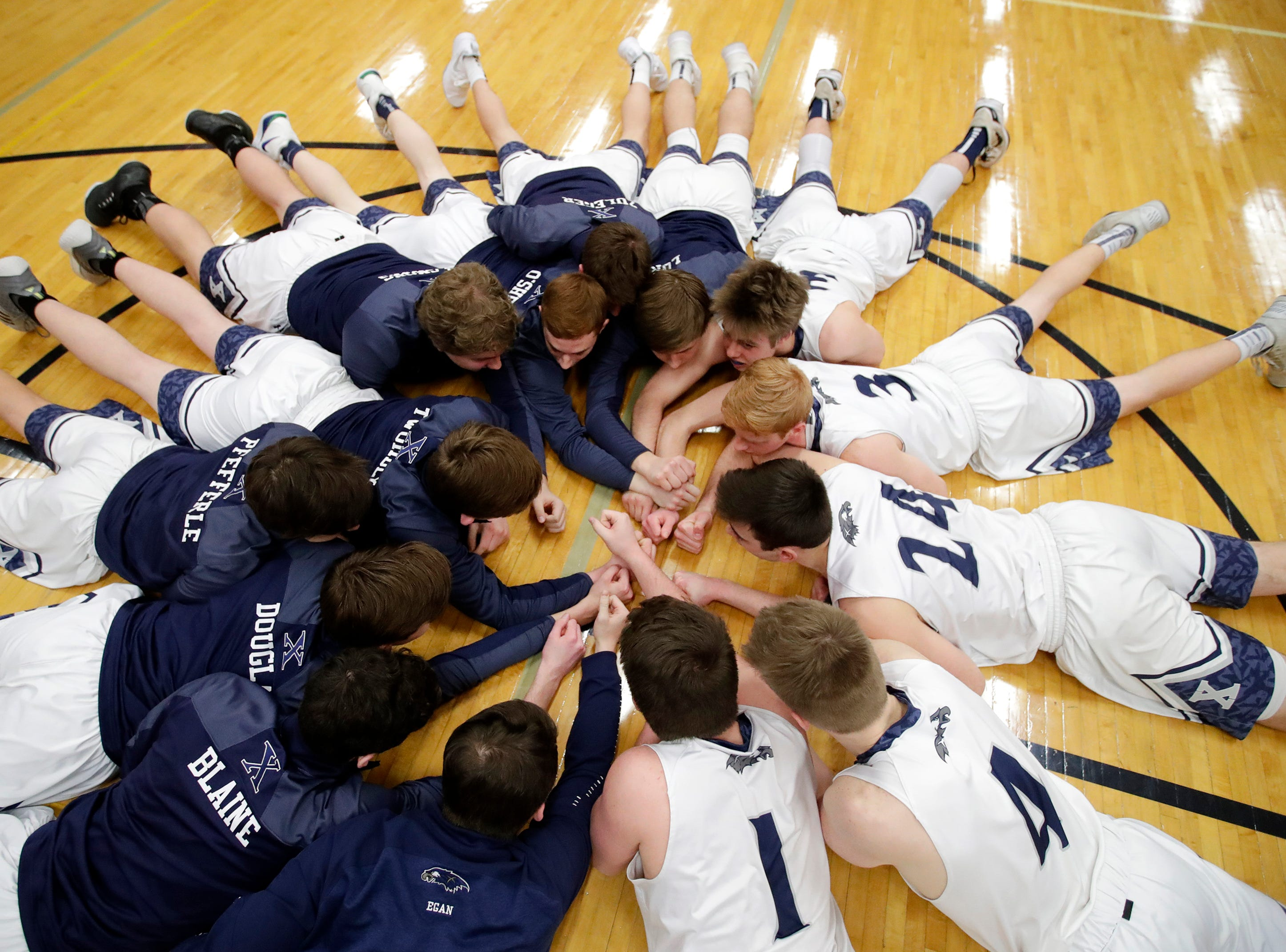 Xavier High School players get into a huddle on the ground after their lineup against Seymour High School was announced Friday, Feb. 8, 2019, in Appleton, Wis.Danny Damiani/USA TODAY NETWORK-Wisconsin