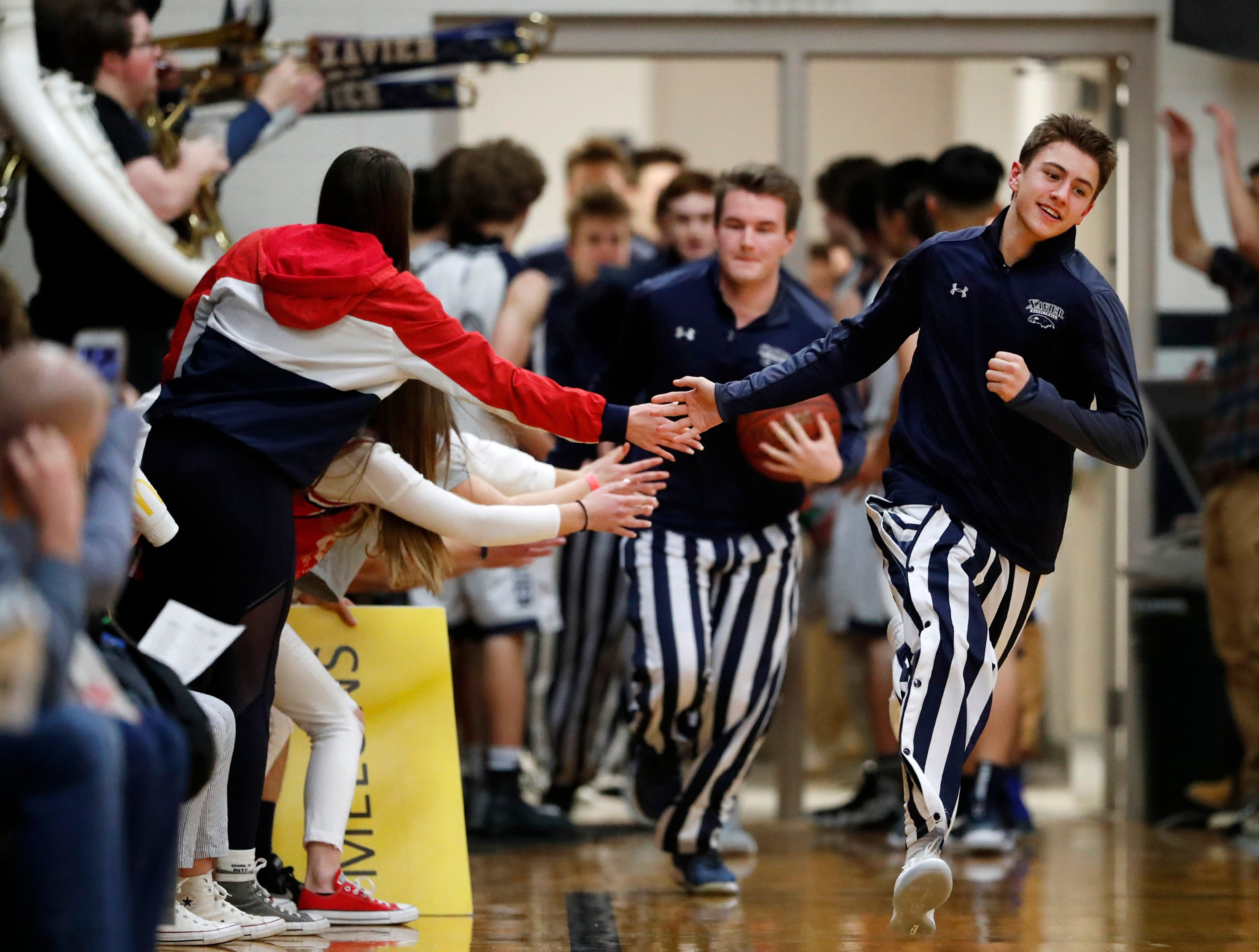 Xavier High School players high five the student section as they take to the court against Seymour High School Friday, Feb. 8, 2019, in Appleton, Wis.Danny Damiani/USA TODAY NETWORK-Wisconsin
