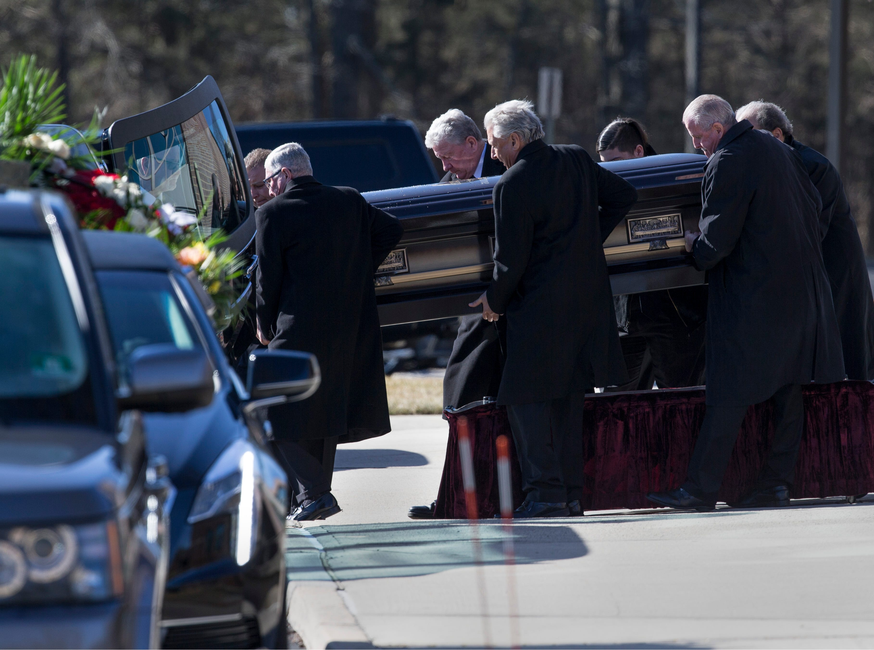 Pallbearers carry the casket of Denise Bartone outside the Co-Cathedral of St. Robert Bellarmine after the ceremony to celebrate her life took place.   