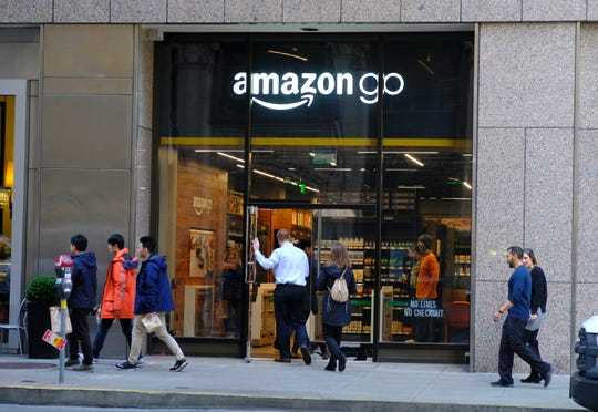People walk past and into an Amazon Go store in San Francisco. Get ready to say good riddance to the checkout line. A year after Amazon opened its first cashier-less store, startups and retailers are racing to get similar technology in other stores throughout the world, letting shoppers buy groceries without waiting in line.