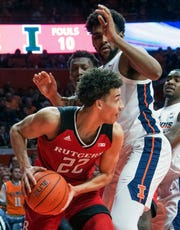 Rutgers guard Caleb McConnell (22) tries to get around Illinois center Adonis De La Rosa