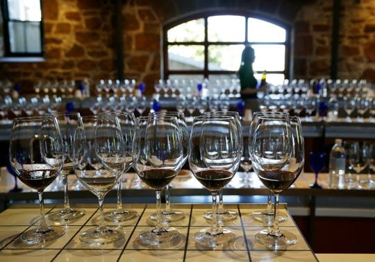 A server fills wine glasses in St. Helena, Calif. While the new tax law gave small business owners new tax breaks including a 20 percent deduction in income for many sole proprietors, partners and owners of S corporations, Congress took back deductions for entertainment expenses, employee transit benefits and what are called net operating loss carrybacks.