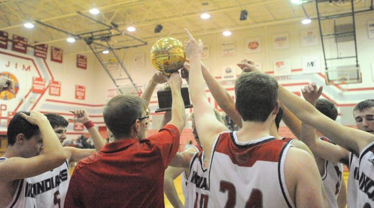 Jim Ned boys basketball coach Eric Phelps, center, holds up the district championship trophy following the Indians' 53-44 win over Colorado City on Friday, Feb. 8, 2019 at Bill Thornton Arena.