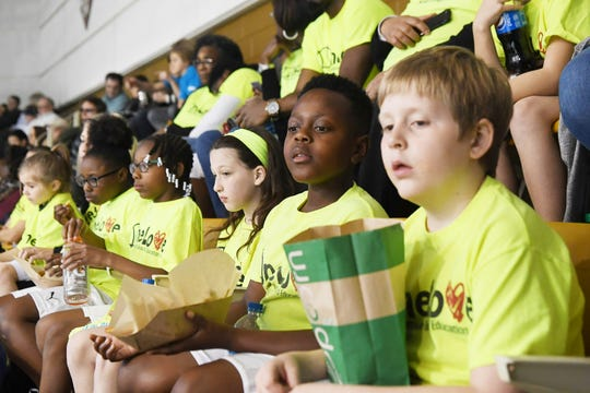 Children with the One Love tennis organization watch the first day of Fed Cup competition between the US and Australia Feb. 9, 2019.