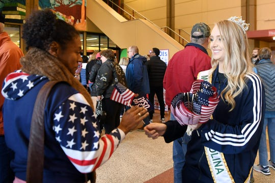 Jessica Lucas, Miss North Carolina US International, hands a US flag to Adelia Hodge, of Greenville, as crowds pour into the US Cellular Center in Asheville during the first day of competition between the US and Australia Feb. 9, 2019.