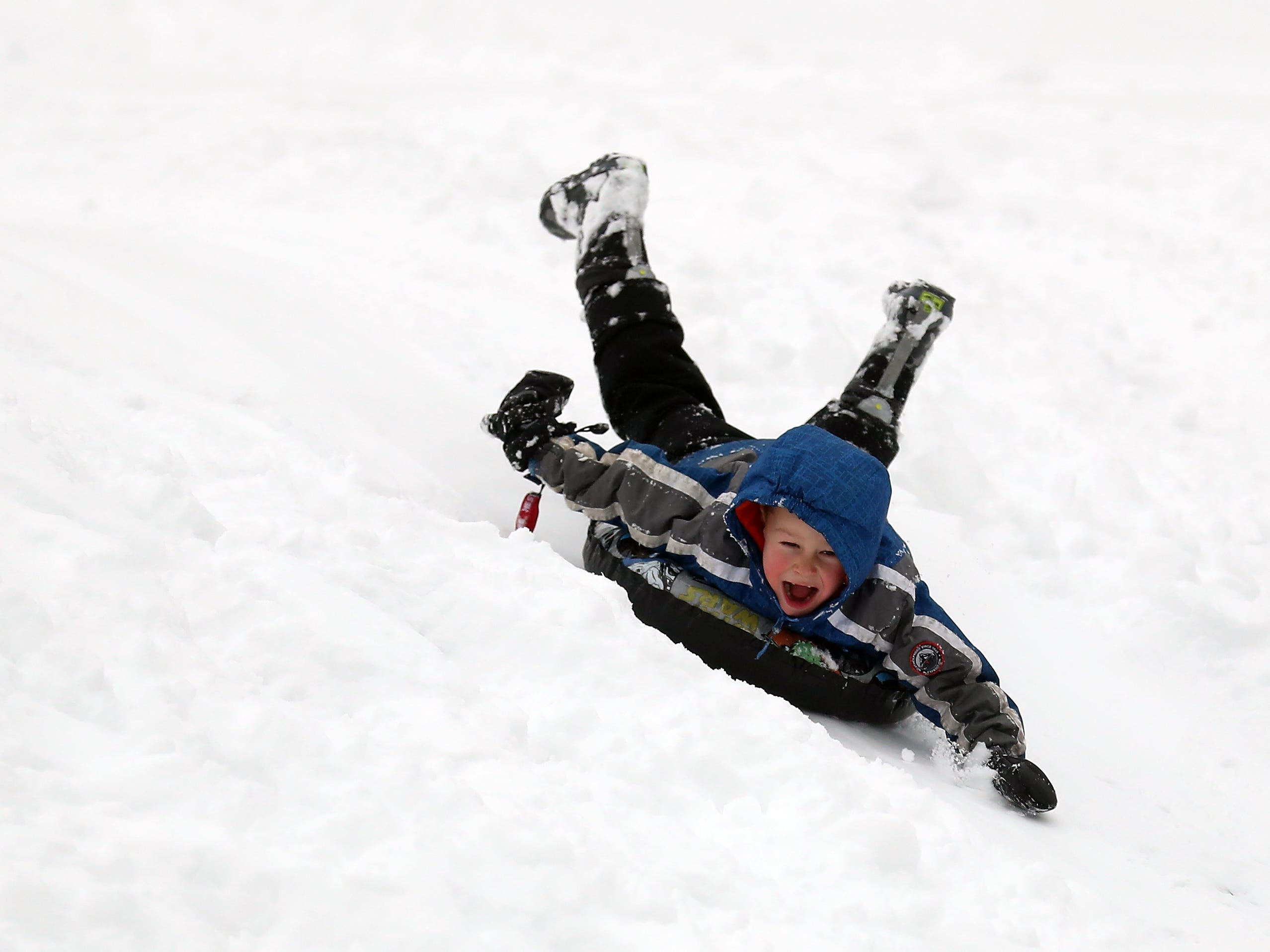 Killian Smart, 5, gives a yell as he zooms down the hill at Silver Ridge Elementary School in Silverdale on Saturday, February 9, 2019.