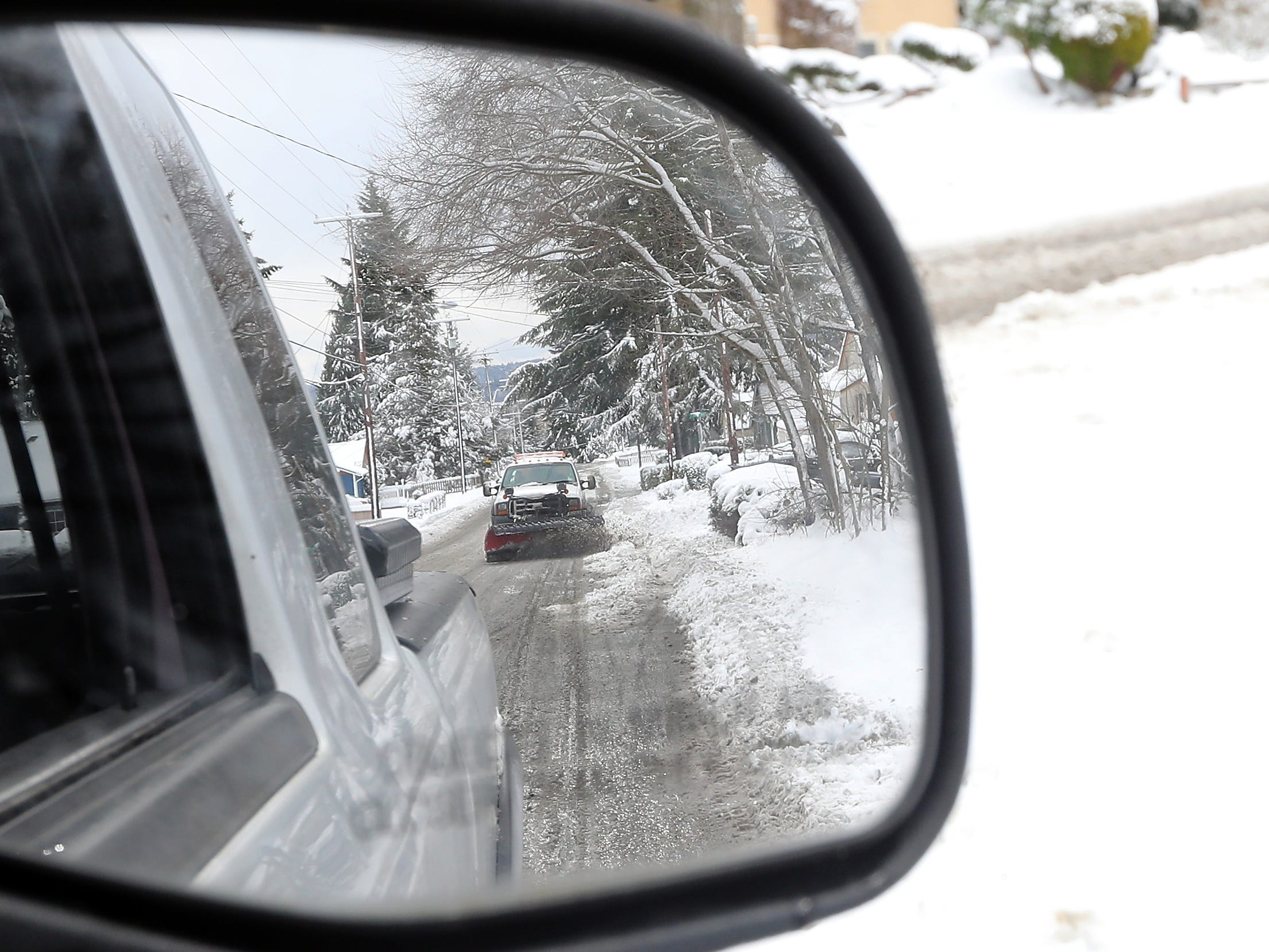 A Bremerton City plow is rejected in a side mirror as it plows Cherry Ave. in Bremerton on Saturday, February 9, 2019.