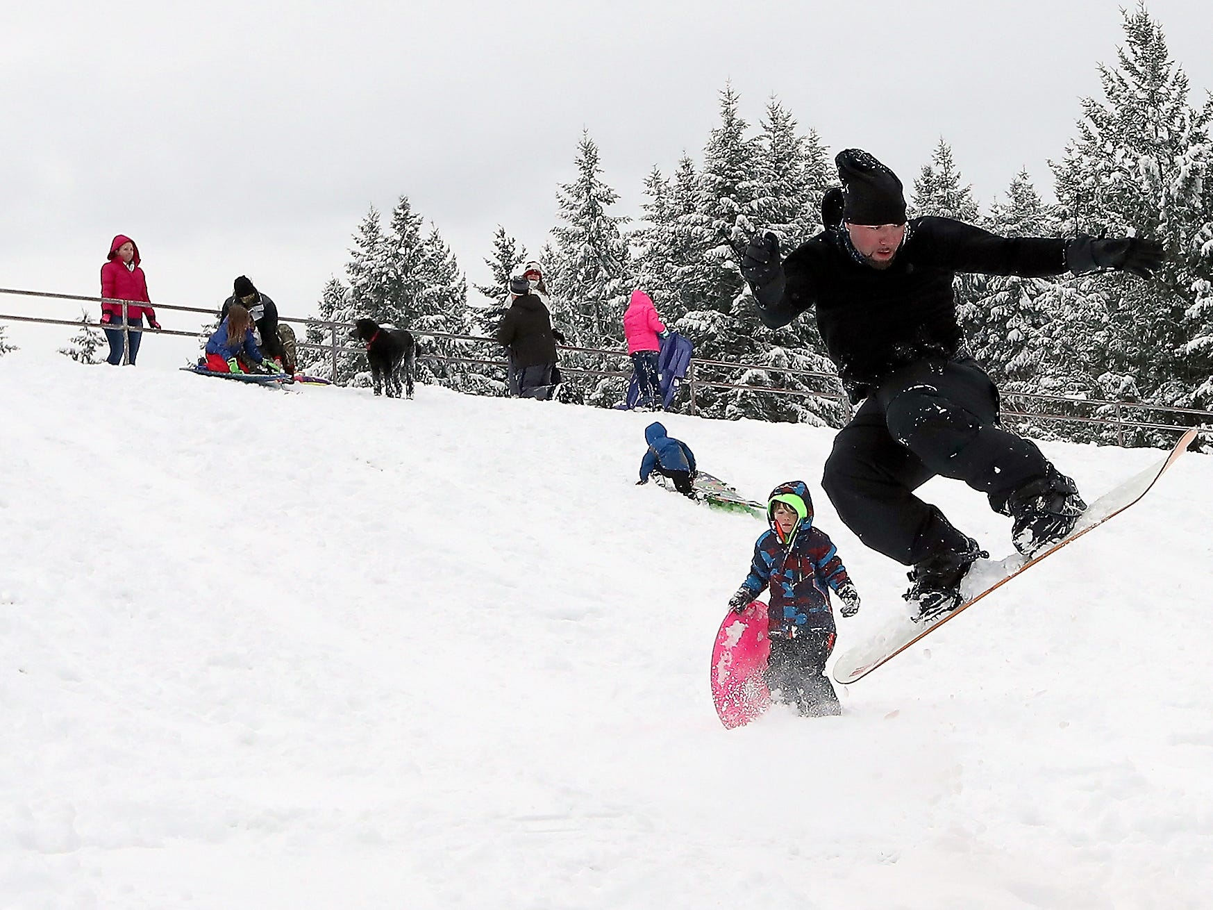 Josh Fairchild hits a jump while snowboarding down the hill at Silver Ridge Elementary School in Silverdale on Saturday.