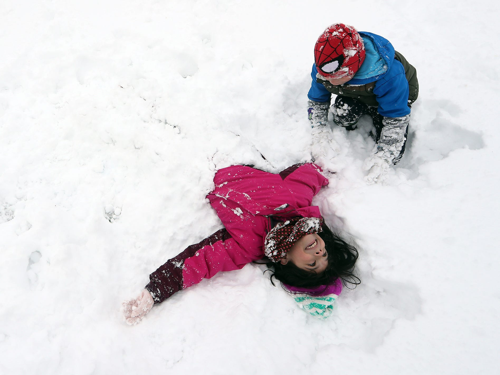 Sebastian Fletcher, 7, buries sister Peyton, 9, in the snow at Evergreen Rotary Park in Bremerton on Saturday, February 9, 2019.