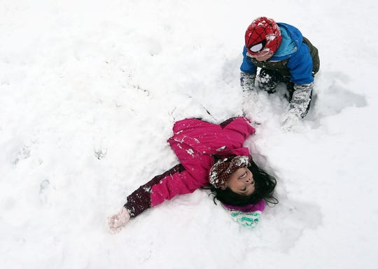 Sebastian Fletcher, 7, buries sister Peyton, 9, in the snow at Evergreen-Rotary Park in Bremerton on Saturday.