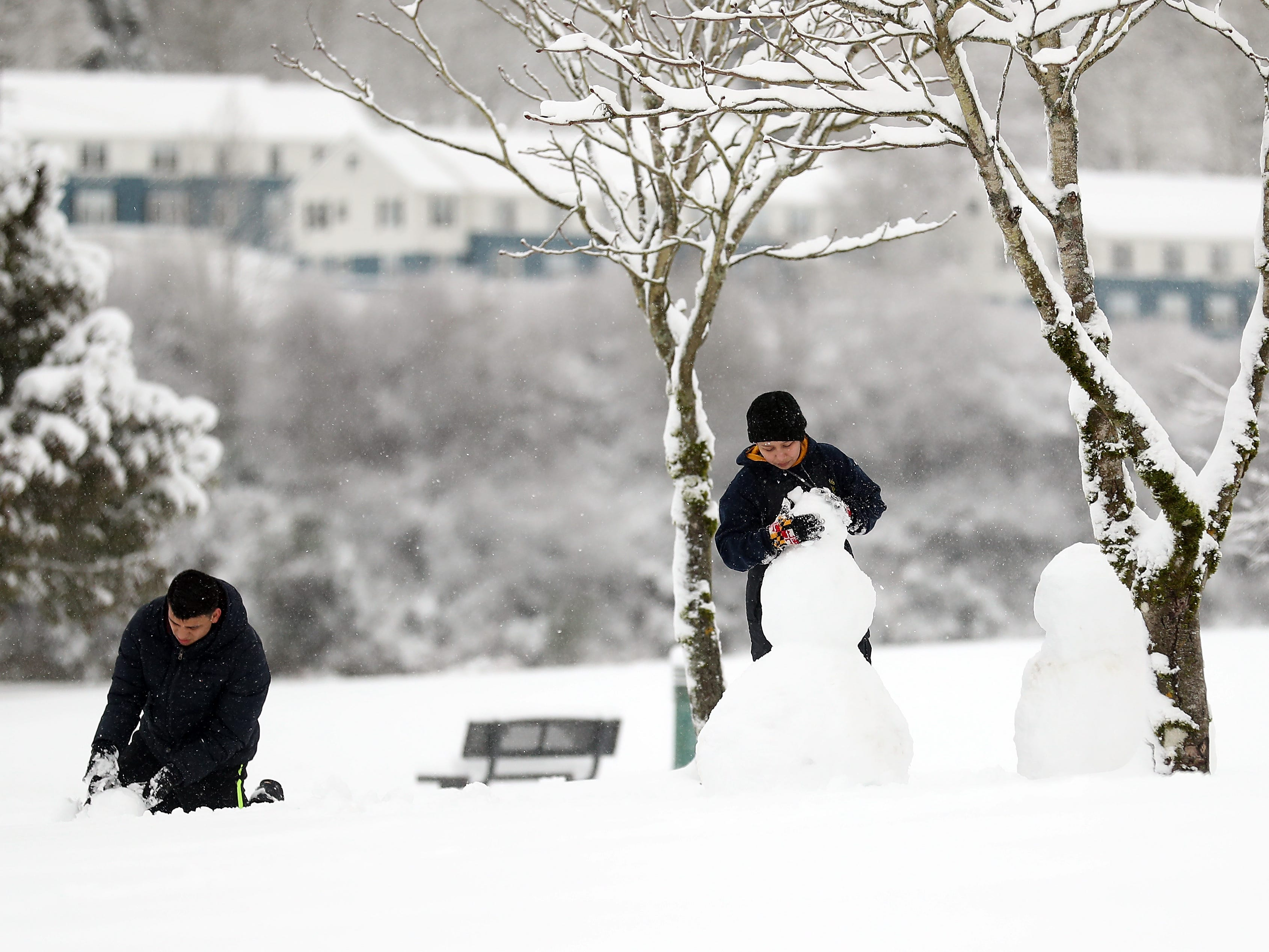 Cristian Flores and his wife Ashley build a pair of snow people in Evergreen Rotary Park in Bremerton on on Saturday, February 9, 2019.